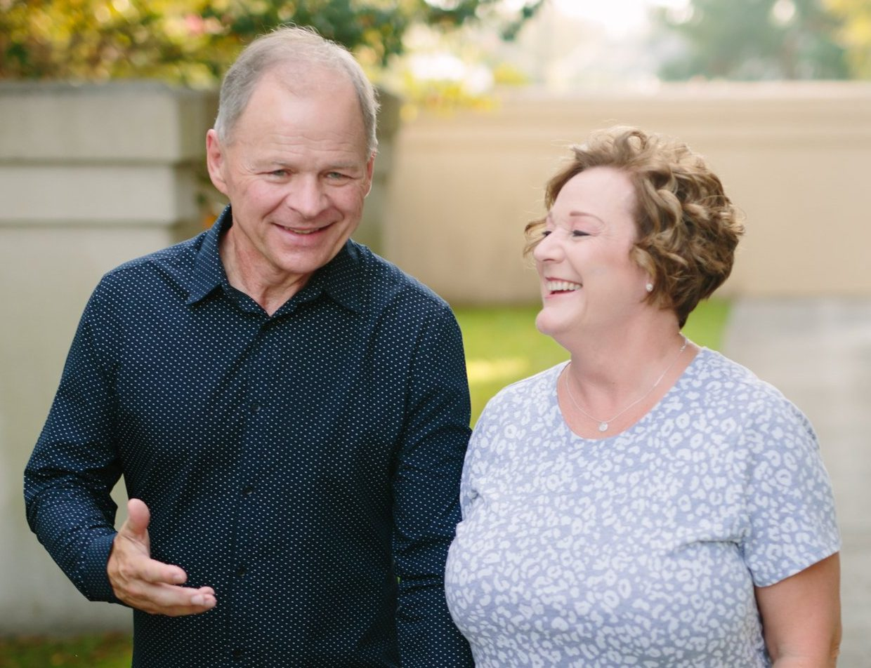Image of Pastor Scott & Trish Forrest walking together in the church campus. Pastor Scott is talking with a smile and Trish is laughing.